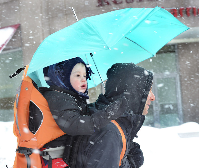 Two-year-old Spencer Hight enjoys his backpack ride with his dad, Scott, and mother, Elizabeth, (not seen) as they enjoy their visit to Portland from Chicago during Friday's snowstorm. Portland has now received 39.4 inches of snow so far this winter.