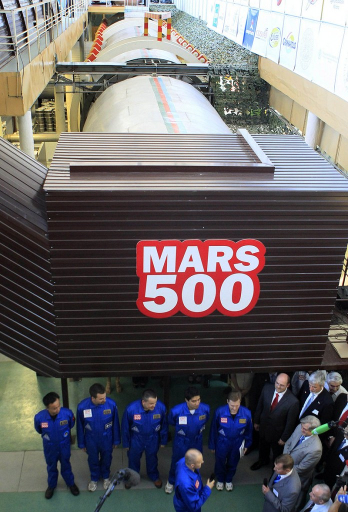 Six researchers, dressed in blue, prepare on June 3, 2010, to enter the steel capsule in which a space flight to Mars will be simulated. The 520-day 'flight' is about half completed, and a 'Mars landing' is scheduled for Feb. 12.