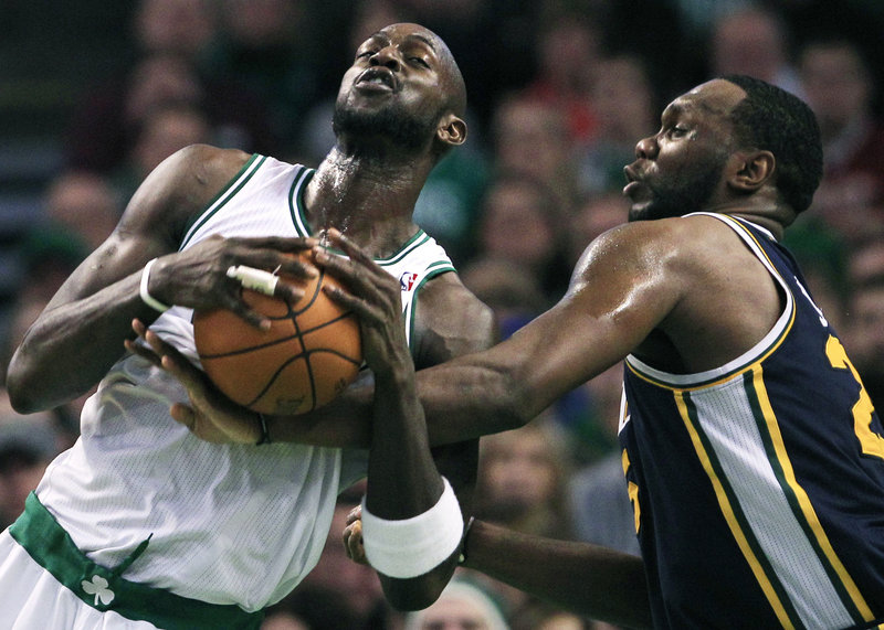 Al Jefferson, right, of the Utah Jazz reaches in and fouls Kevin Garnett on a drive Friday night at Boston. Garnett had a team-high 21 points in the Celtics' 110-86 win.
