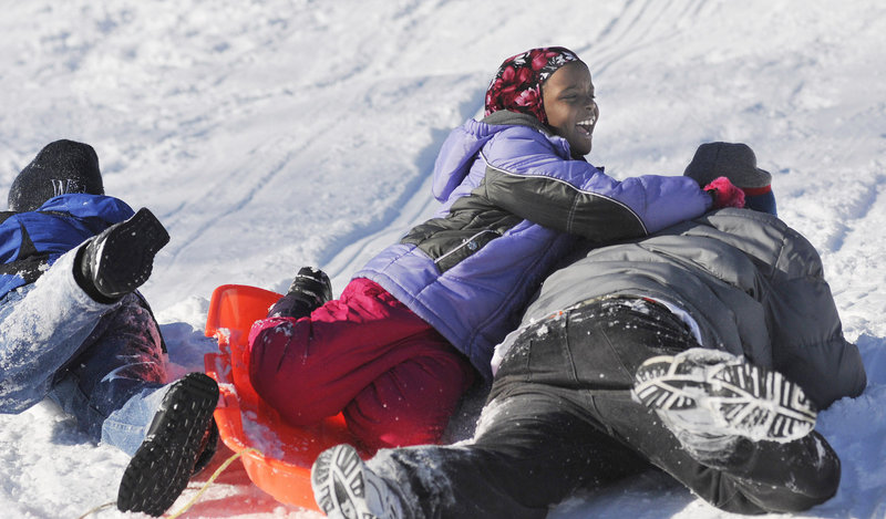 Fatuma Mohamed, 8, laughs as she crashes on a sled with her brothers Hassan Mohamed, 11, left, and Abdi Mohamed 16, of Portland during the WinterKids event to introduce immigrant and refugee families to winter activities Saturday. The Mohamed family is originally from Kenya.