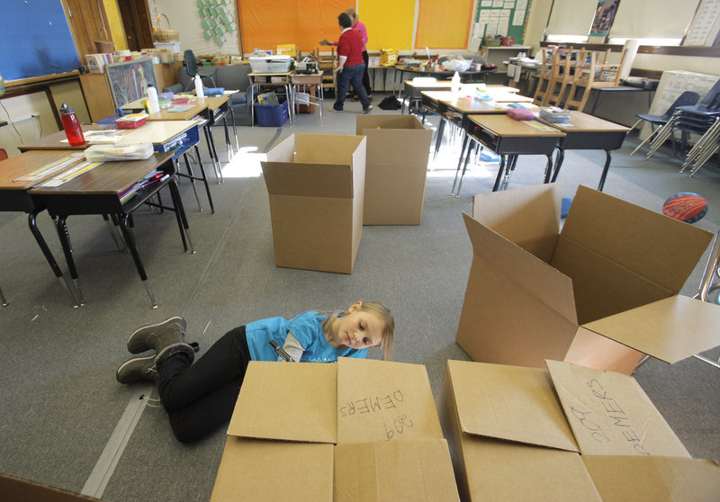 Maddie Kerr, a third-grader at Nathan Clifford School, writes her teacher's name on a cardboard carton in her classroom on Saturday. Students, teachers and parents boxed up items in preparation for the move to Ocean Avenue School.