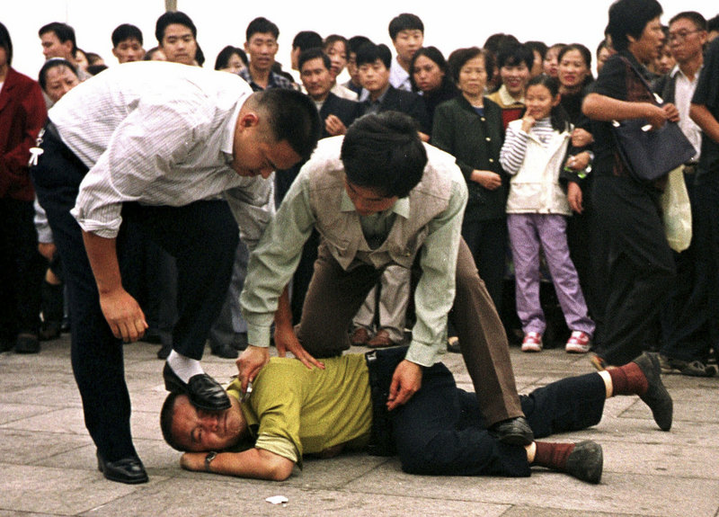 "Police detain a Falun Gong protester in Beijing in 2000. Human Rights Watch decries ""the near-universal cowardice in confronting China's deepening crackdown on basic liberties."""
