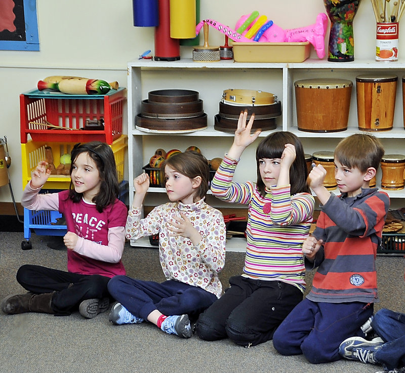Longfellow Elementary students Ashlyn Lowe, left, Fiona Larsson, Glynis O'Meara and Jack Lagrange learn to sing different parts of a choral work by using hand signs to distinguish each part.