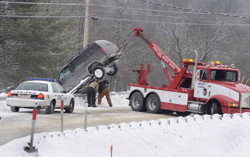 A wrecker operator removes a vehicle from a guardrail along Route 114 in Gorham on Tuesday. Early in the day, precipitation iced up on many roadways in Greater Portland, wreaking havoc with the morning commute.