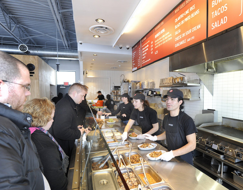 Danny Leon, on right, and Julia Calder, center, serve customers at the Chipotle Mexican Grill, a chain restaurant in South Portland.