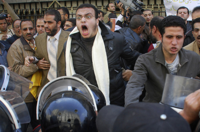 Protesters are confronted by riot police as they demonstrate in downtown Cairo on Tuesday. Hundreds of anti-government protesters marched in the Egyptian capital chanting against President Hosni Mubarak and calling for an end to poverty.