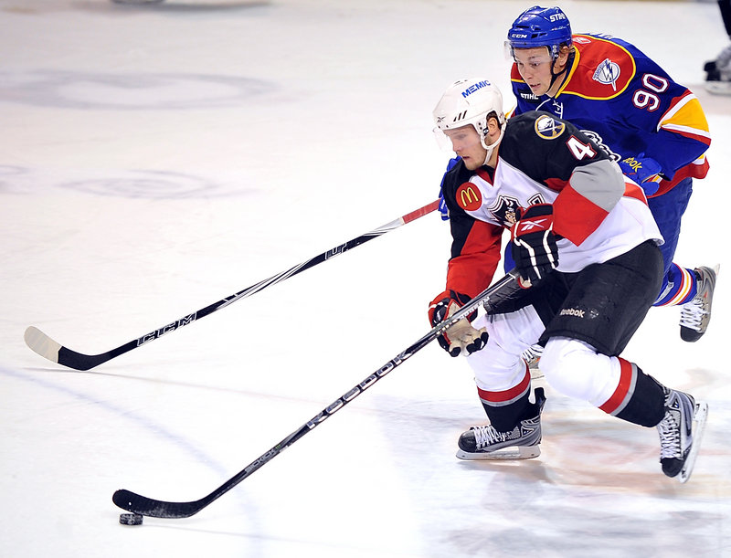 Portland's Alex Biega tries to break away from Norfolk's Johan Harju in the first period. Call-ups and injuries shortened Portland's bench for the game.