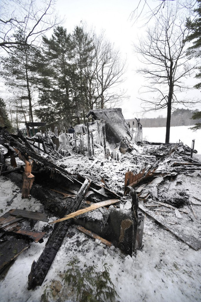 Charred debris remains after an early-morning house fire on Highland Lake. The occupants escaped safely.