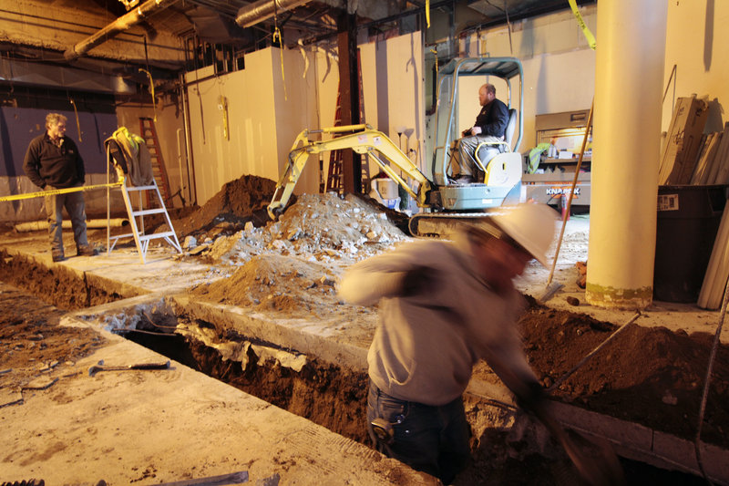 Workers excavate the future site of a Five Guys Burgers and Fries on Fore Street in Portland. The chain restaurant will open this spring.