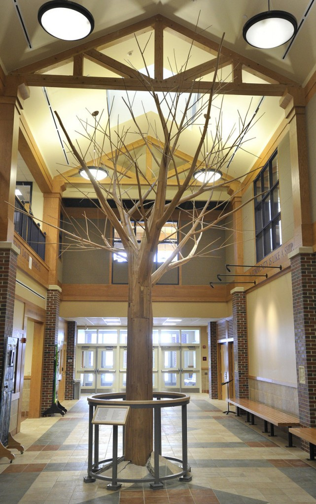 """Aaron Stephan's """"RE: turn,"""" made of lumber from trees salvaged from the bottom of Moosehead Lake, stands in the atrium of Westbrook Middle School."""