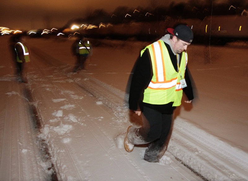 Assistant Director Rob Parritt and others from the Oxford Street Shelter trudge along railroad tracks near Commercial Street as they take a survey of homeless people Wednesday.