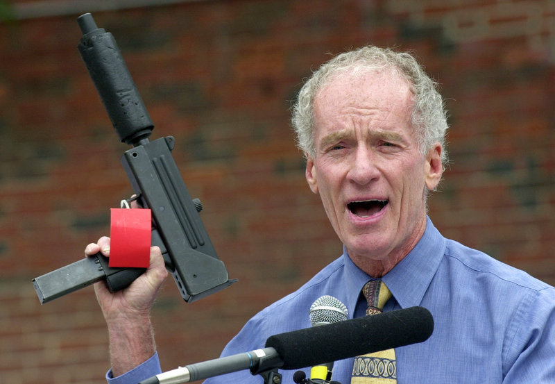 Former Portland police chief Michael Chitwood holds a MAC-10 automatic pistol with a silencer and an extended magazine seized in a raid by his deparment.