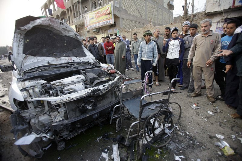 Residents of the Shula neighborhood of Baghdad stand near a destroyed car and wheelchair after Thursday's attack. Violence in the past week has mainly targeted Shiites and security forces.