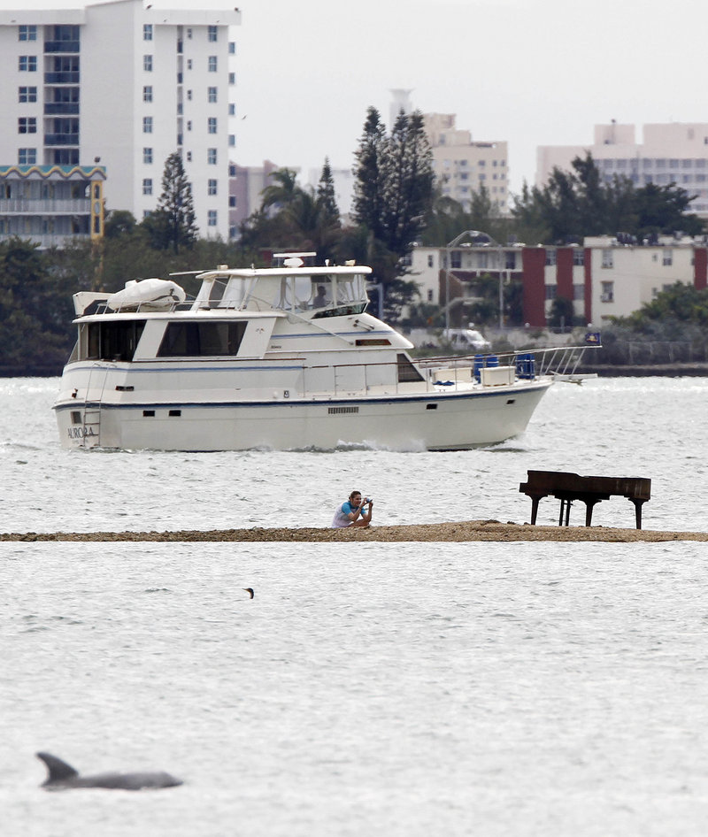Freelance photographer Karla Murray of New York photographs a grand piano that appeared on a sandbar in Biscayne Bay, Miami. The piano was placed at the highest point of the sandbar so that it's not underwater during high tide.
