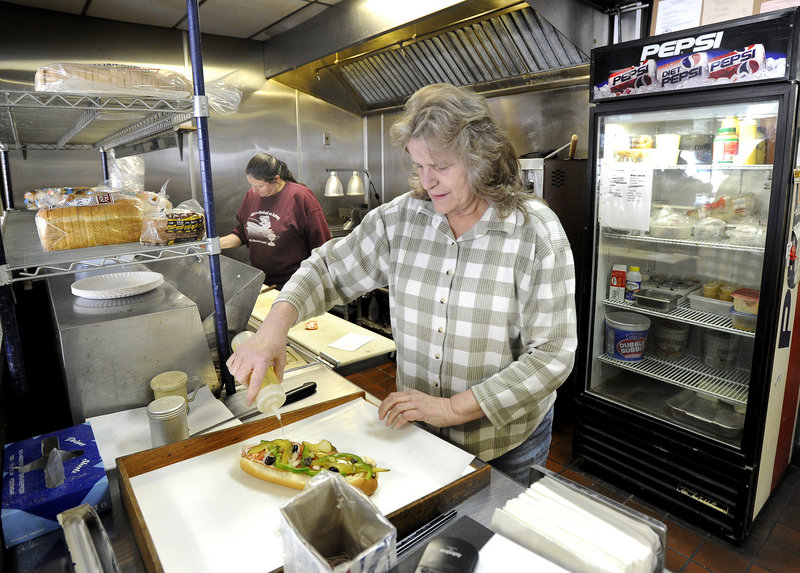Sheila Cunningham assembles one of her last Italian sandwiches as an employee of Terroni's Market during her shift on Friday.