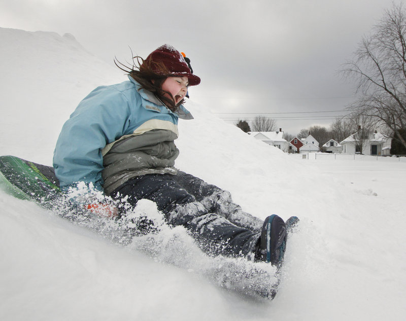 "Sarah Younk, 9, slides at Walton Field on Saturday on the opening day of the Auburn Winter Festival. The hill is part of a snow playground created for the ""celebration of everything winter"" that continues through Feb. 6."