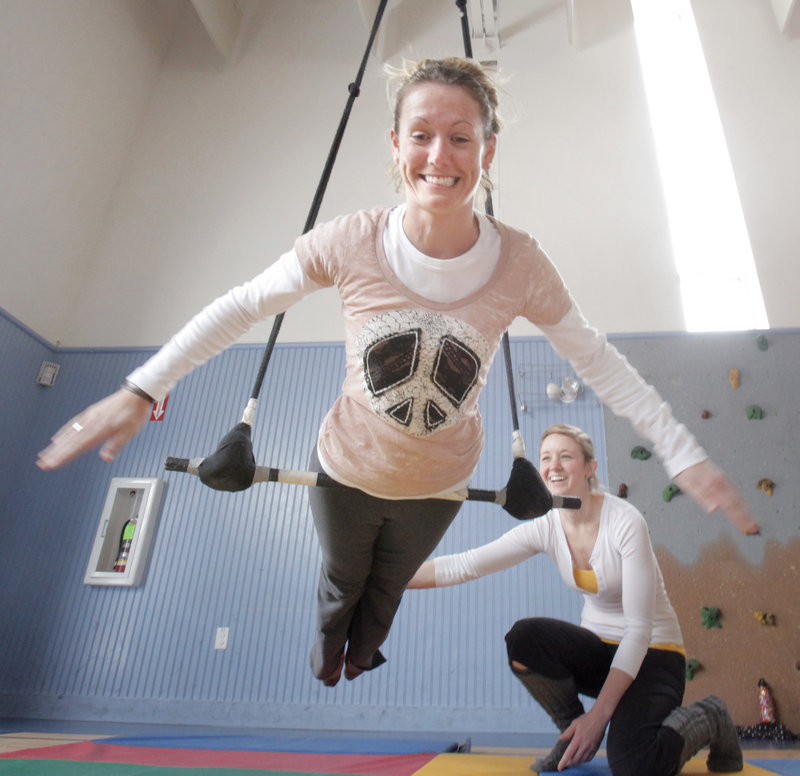 Assisted by Casey Turner, Jill Newell finds her balance point on a trapeze. The 17 workshop attendees were encouraged to play and discover on the apparatus.