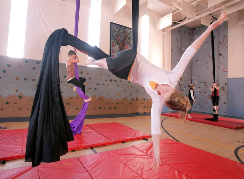Casey Turner of Portland balances with her legs wrapped in an aerial fabric during a workshop at the Breakwater School in Portland on Saturday. Participants could learn skills on aerial fabric and also circling trapezes. In the background, Jane Frederick of Portland climbs an aerial fabric.