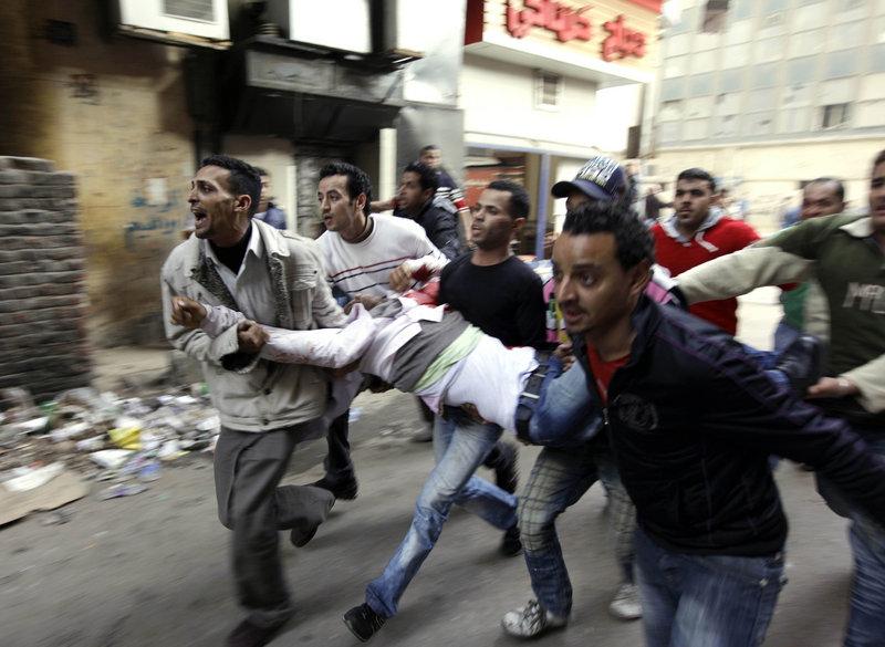 Egyptians carry an injured protester after clashing with police in Cairo on Saturday.