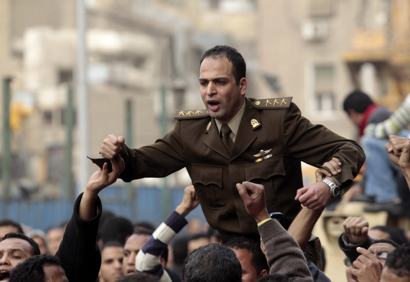 Egyptian anti-government protesters carry on their shoulders an Egyptian army officer who joined them in their protest in Tahrir square in Cairo, Egypt, on Saturday.