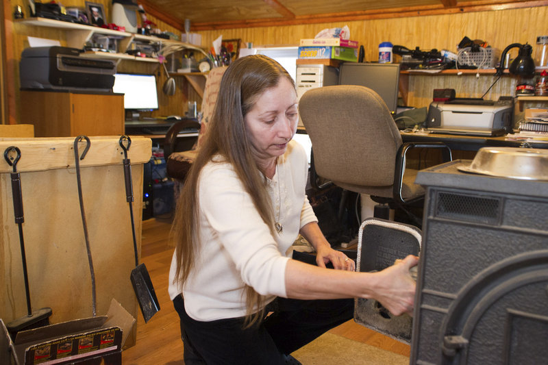 Valerie Houde fills her wood stove while waiting for a dial-up Internet connection in East Burke, Vt.