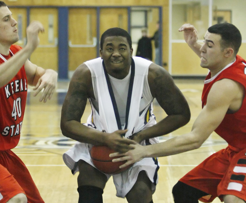 Otis Smith of the University of Southern Maine pulls a rebound away from Keene State's Nicco DeMasco, left, and Cody Snow during a Little East Conference men's basketball game Saturday. Keene State held off the Huskies, 72-67.