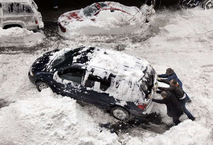 Three men attempt to free an automobile from the snow on New York's Upper West Side today.