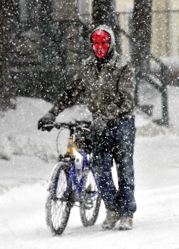 SNOW PROBLEM: Leonard Greeley walks his bike along Ticonic Street in Waterville during a windy snowstorm on Wednesday. Greeley said he did not mind using a bike in the snow saying,