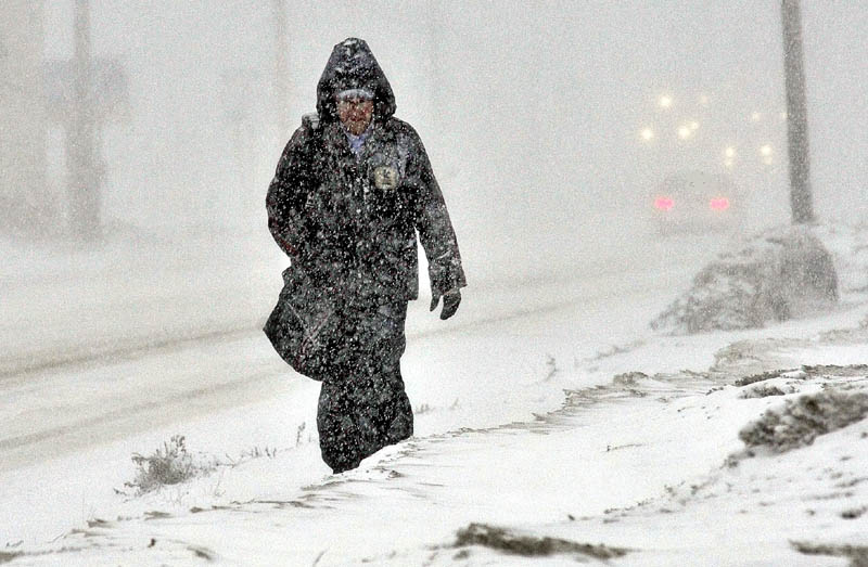 Staff photo by David Leaming WEATHER OR NOT: Mail carrier Jim Waters makes his way along Kennedy Memorial Drive in Waterville during the snowstorm on Wednesday. Asked about the working outdoors during inclement weather Waters shrugged his shoulders and said,