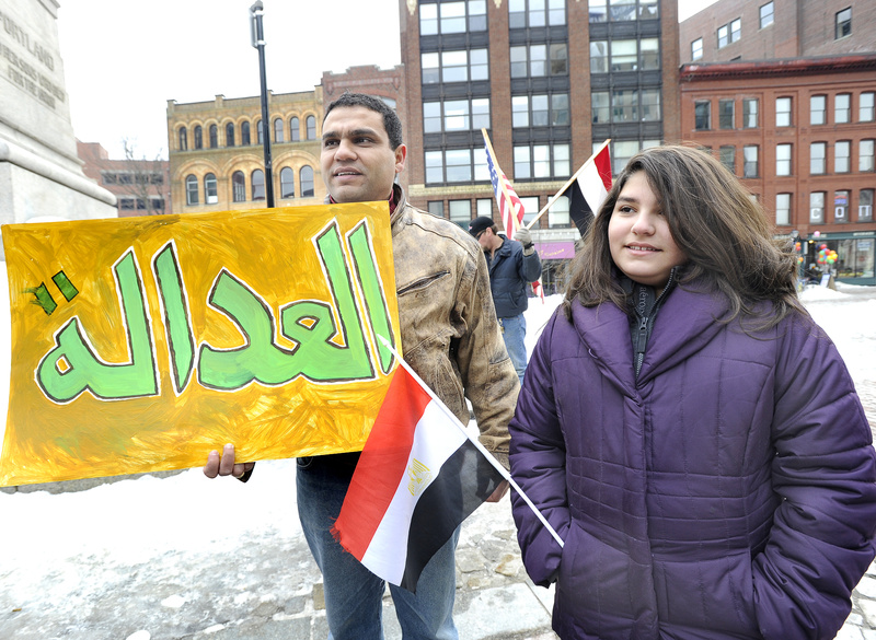 Egyptian Mody Botros, who lives in Bridgton, and his 12-year-old daughter, Amanda, attended a rally in Monument Square on Saturday in support of democracy in Egypt. Botros' sign says justice in Arabic.