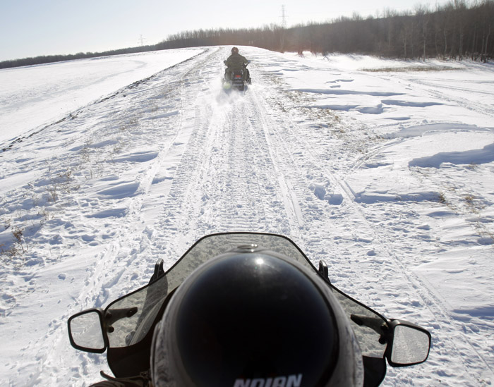 In this Feb. 10, 2011, photo, U.S. Border Patrol agents Glenn Pickering, front, and Janice Jones ride snowmobiles along the St. Lawrence River in Massena, N.Y.