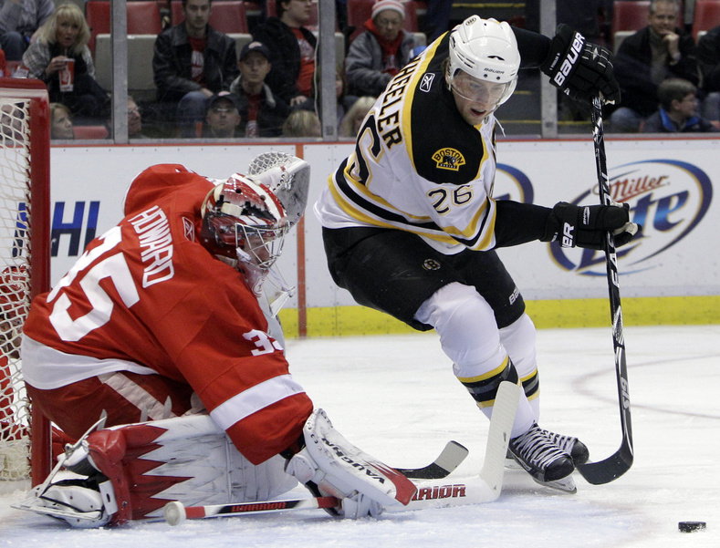 Blake Wheeler of the Bruins controls the puck in front of Red Wings goalie Jimmy Howard in Sunday's game at Detroit. Detroit won, 4-2.