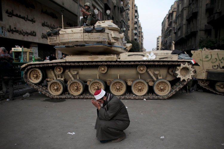 An Egyptian cries in front of on army tank in Tahrir, or Liberation square, in Cairo today, where several thousand supporters of President Hosni Mubarak, including some riding horses and camels and wielding whips, clashed with anti-government protesters.