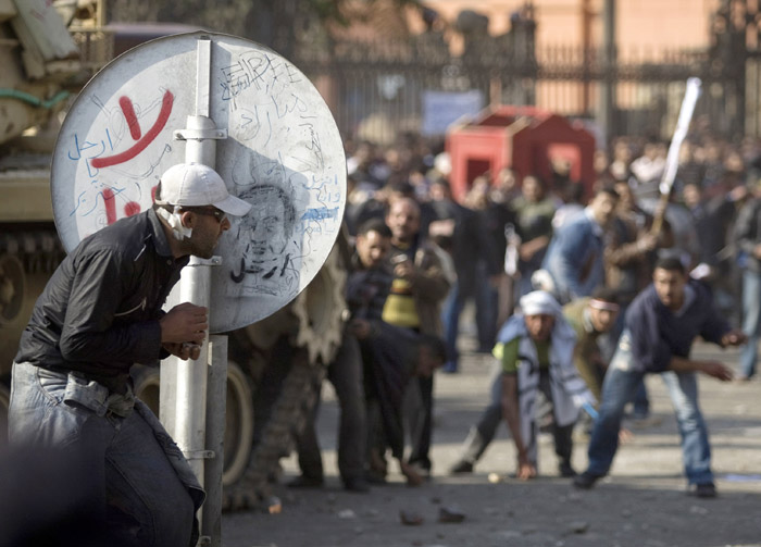 An anti-government protester shelters behind a road sign as pro-government demonstrators throw rocks in Cairo today.