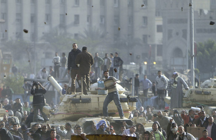 Stones fly through the air as supporters of President Hosni Mubarak, foreground, fight with anti-Mubarak protesters, rear, standing on army tanks in Cairo.