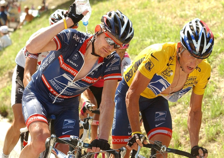 A July 22, 2004, photo of overall leader Lance Armstrong, right, straining in an ascent during the 17th stage of the Tour de France cycling race, as teammate Floyd Landis pours water over his neck.