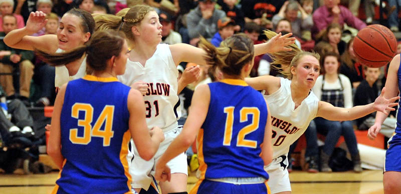REACHING OUT: Winslow's Lynsey Vigue, right, keeps her eye on the loose ball during the third quarter of an Eastern Maine Class B preliminary game against Hermon on Tuesday night in Winslow. Winslow lost 40-33.