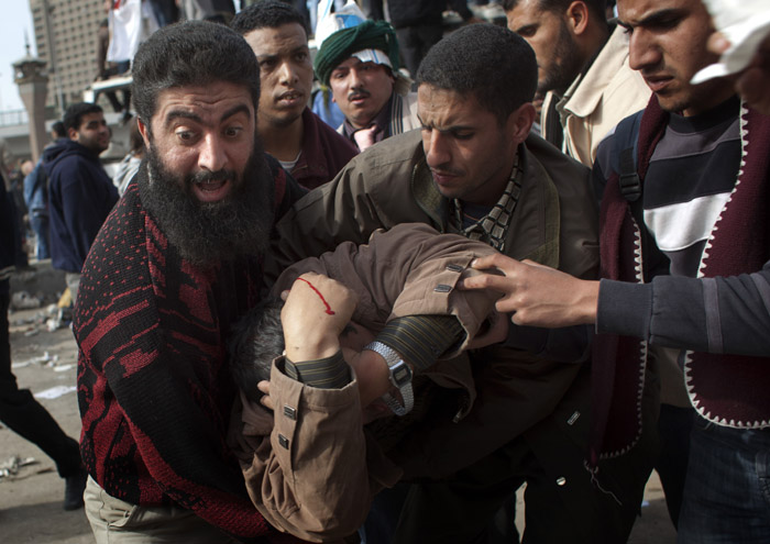 An anti-government protester gets assistance after being wounded during clashes in Cairo today