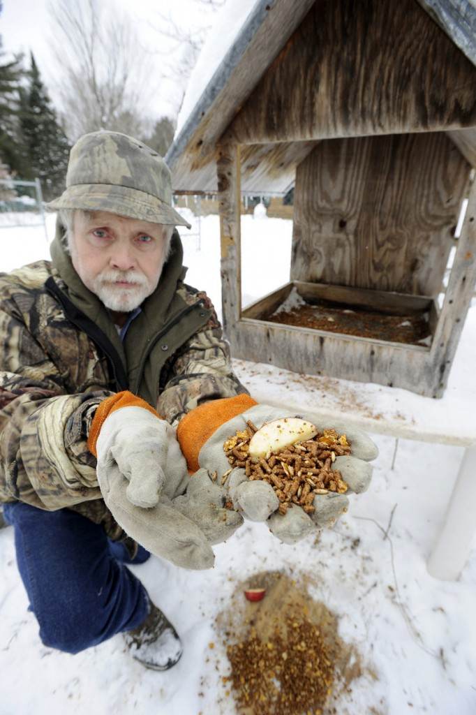 John Chapman shows the feed he puts out once a day for the deer. The mixture – grain, molasses, apples and flaked corn – contains the protein that deer require to be properly nourished.