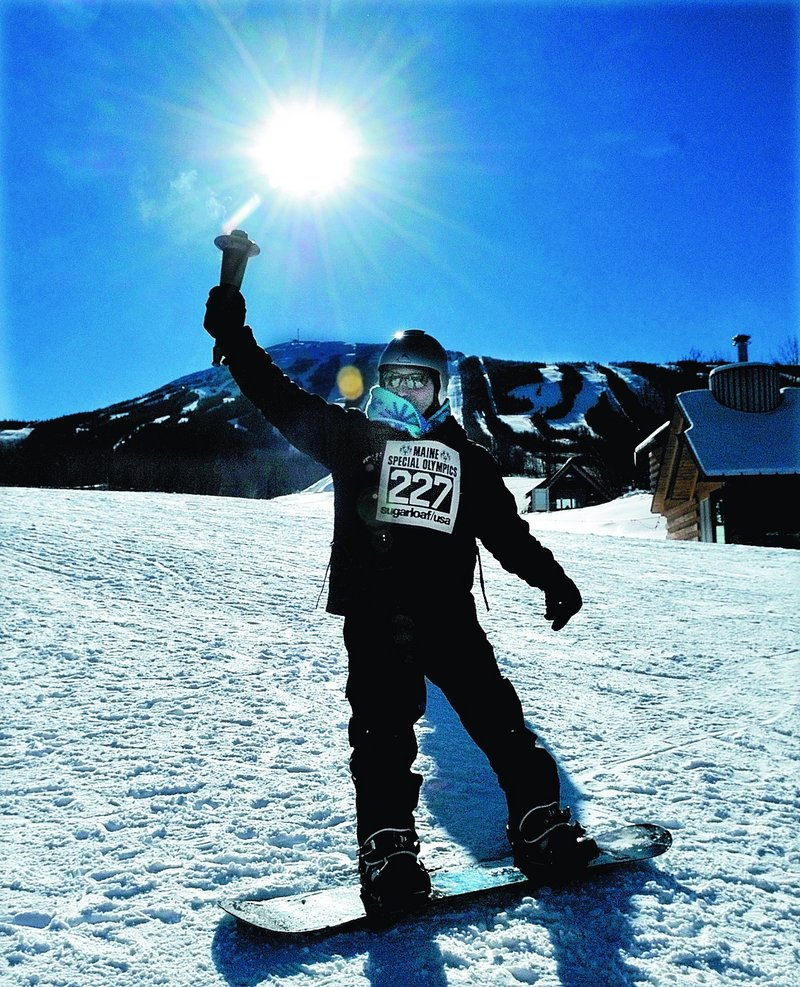 Snowboarder Keith Draper of Greene carries the Olympic torch during the opening cermony at Sugarloaf on Monday.