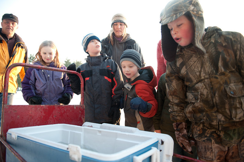 Fish in a cooler at Crystal Lake draw attention. The event's ice fishing derby for kids attracted 950 young anglers.