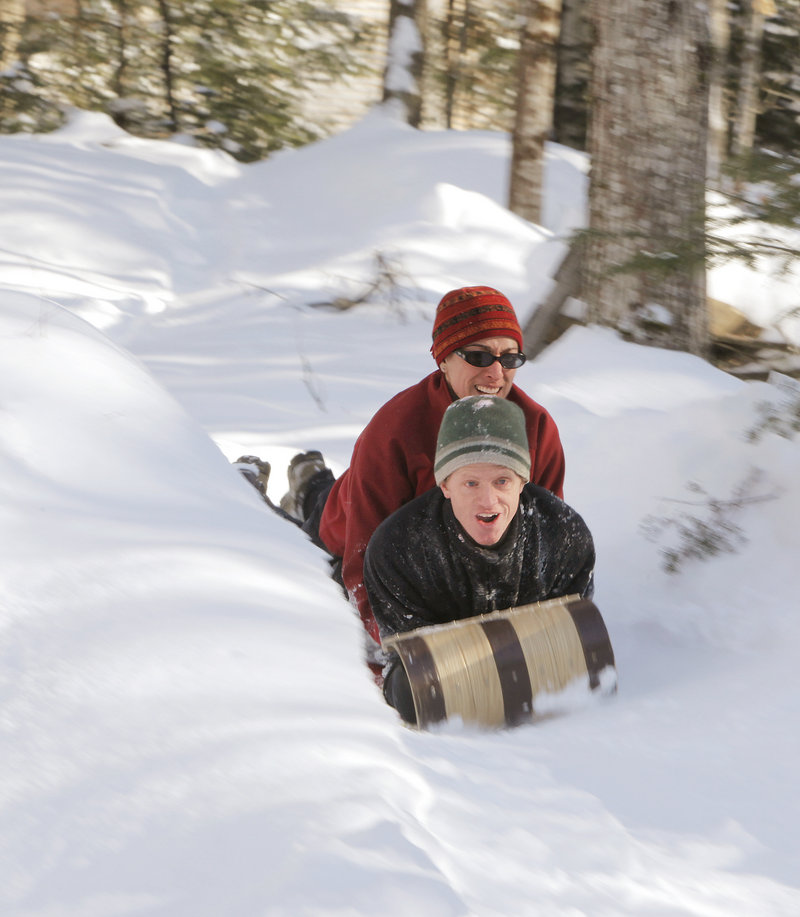 Angela and Andy Russ take a toboggan down the chute. The family also rides on inflated tubes and maneuverable sleds.