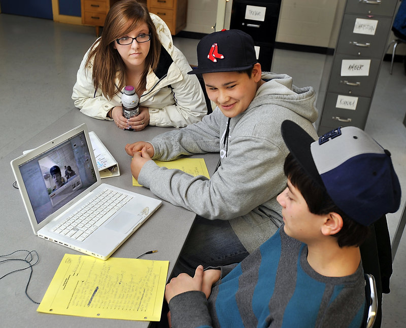 Mentor and aide Chelsea Campbell works with Christian Sawyer, 15, center, and Kristian Gallagher, 14, as they work on the exercise.