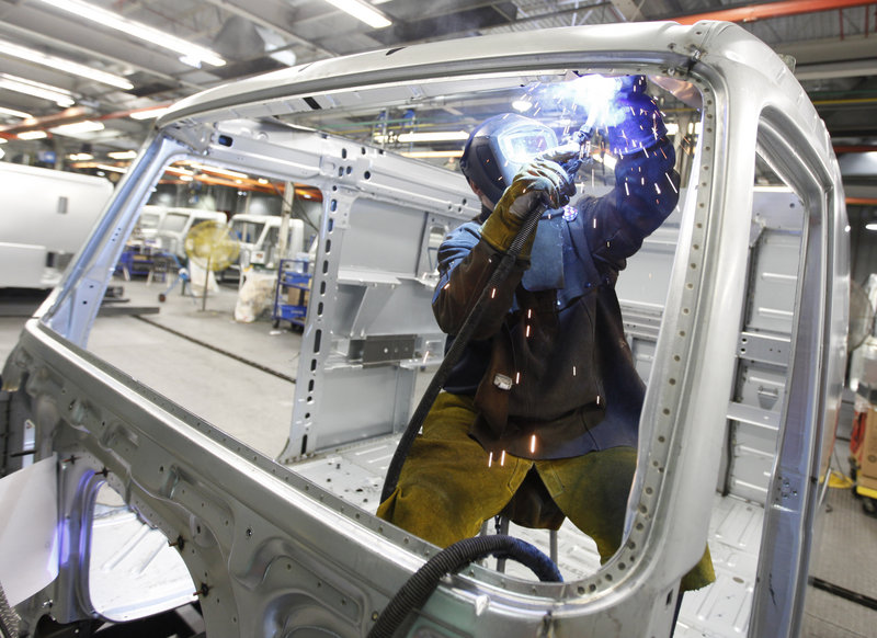 An employee welds the frame of a truck's cab on an assembly line at the Volvo plant in Dublin, Va. The factory sector expanded in January at the fastest pace in seven years as manufacturers reported a sharp jump in new orders.