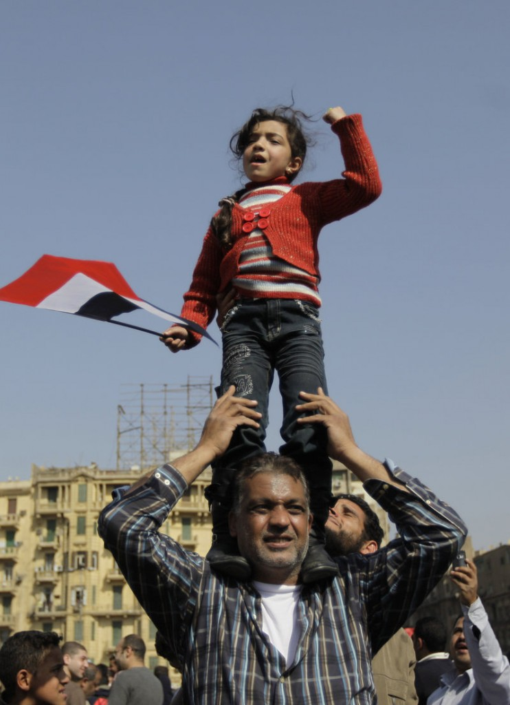 A girl stands tall, pumping her fist in celebration in Tahrir Square.