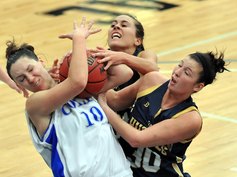 Jules Kowalski, left, of Colby struggles with Kaylie DeMillo, right, and Haley Jordan of the University of Southern Maine for a rebound Tuesday night during their game at Waterville. Colby took charge with a run late in the first half and posted a 74-45 victory.