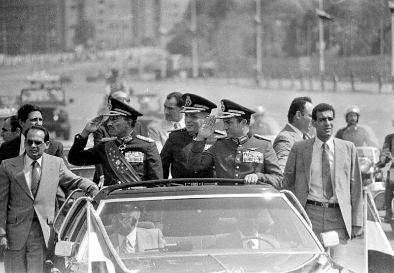 In this photo from 1981, Egyptian President Anwar Sadat, left, salutes from a Cairo motorcade. At right is Vice President Hosni Mubarak, who would become president after Sadat's assassination by Muslim militants in 1981.