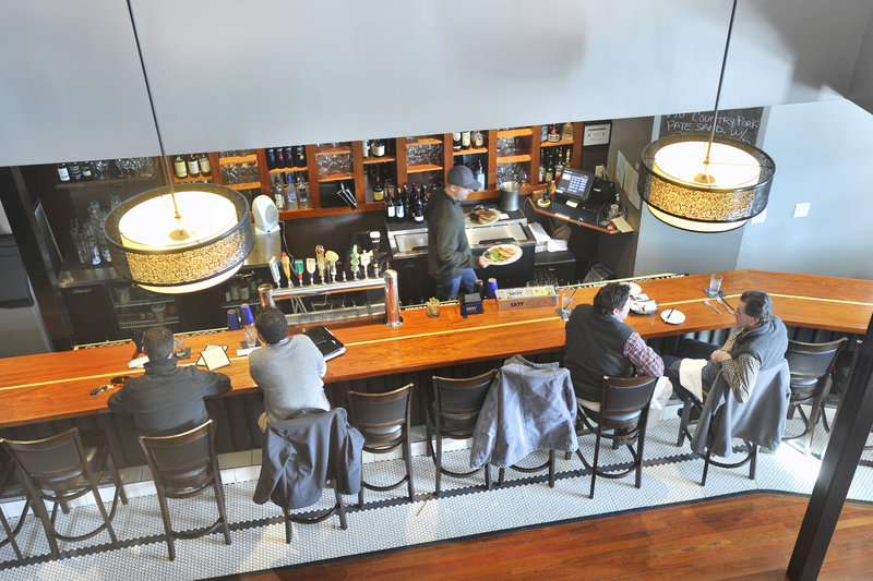 At District, a railed opening on the second floor overlooks the bar and is a comfortable place to perch, people watch and drink a glass from a good wine list.