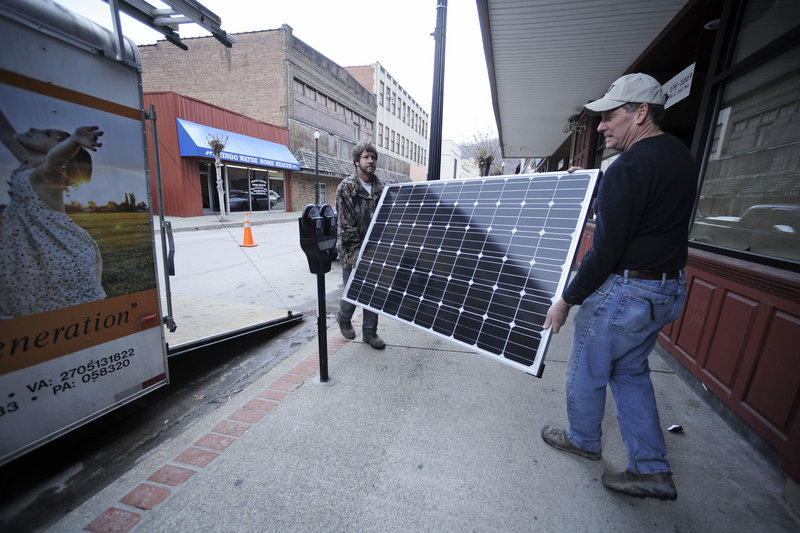 Evell Meade, left, and Mitch Mitchell carry a solar panel into a Williamson, W.Va., office on Wednesday as part of a jobs program focusing on alternative energy.