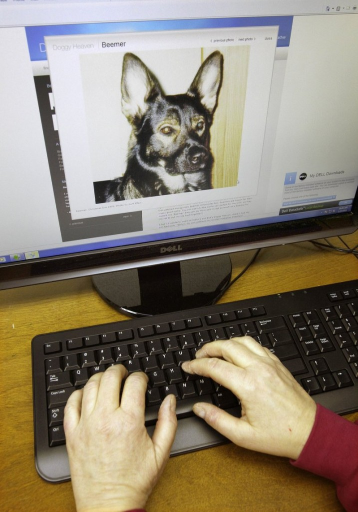 Joann Cencula works on her website Doggy Heaven at her home in Wickliffe, Ohio. On the screen is a photograph of Beemer, one of Cencula's beloved dogs that passed away.